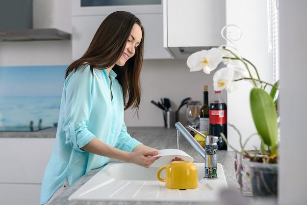 Jovem mulher lavando pratos em frente à janela na luz suave