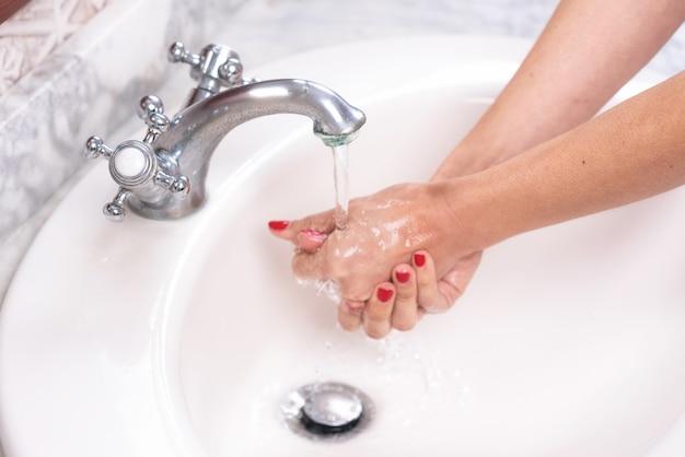 Jovem mulher lavar as mãos, limpeza de mãos, higiene.