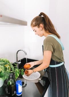 Jovem mulher lavar tomates na pia da cozinha