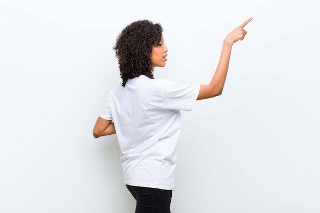 Jovem mulher legal em pé e apontando para o objeto no espaço da cópia, vista traseira