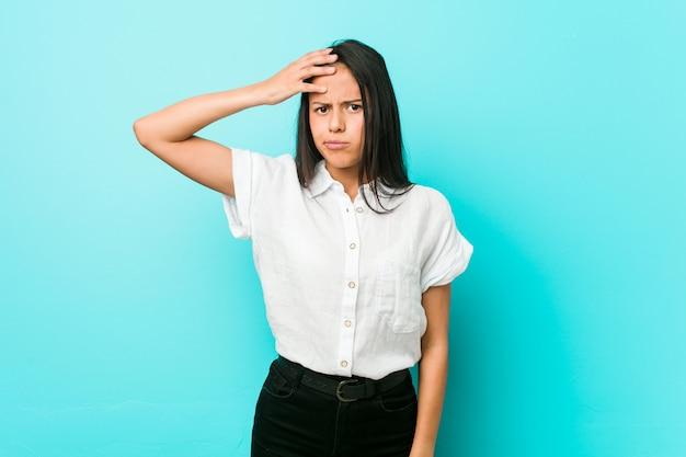 Jovem mulher legal hispânica contra uma parede azul sendo chocada, lembrou-se de uma reunião importante.