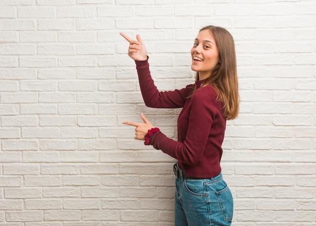 Jovem mulher legal sobre uma parede de tijolos, apontando para o lado com o dedo
