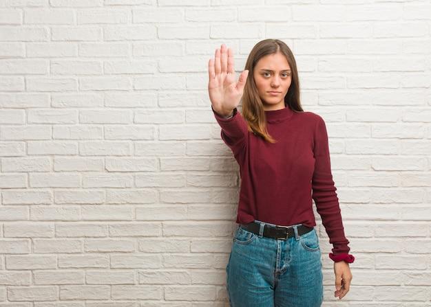 Jovem mulher legal sobre uma parede de tijolos, colocando a mão na frente