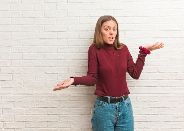 Jovem mulher legal sobre uma parede de tijolos confuso e duvidoso