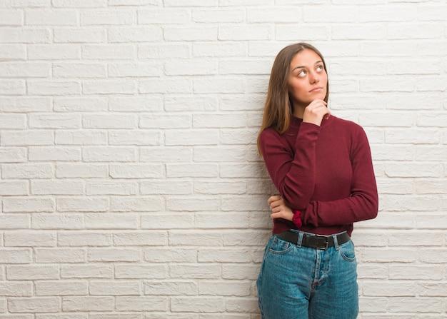 Jovem mulher legal sobre uma parede de tijolos duvidando e confuso