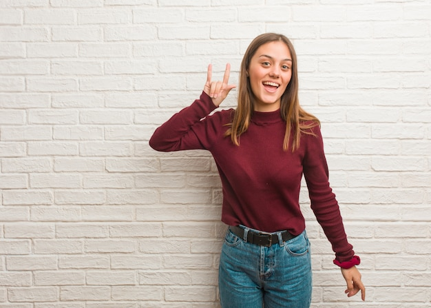 Jovem mulher legal sobre uma parede de tijolos, fazendo um gesto de rocha