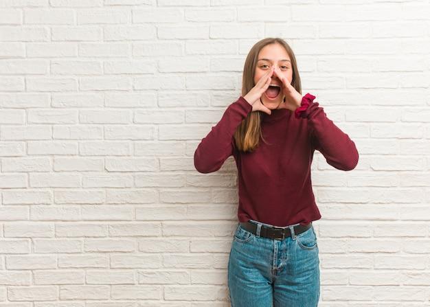Jovem mulher legal sobre uma parede de tijolos, gritando algo feliz para a frente