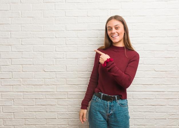 Jovem mulher legal sobre uma parede de tijolos sorrindo e apontando para o lado