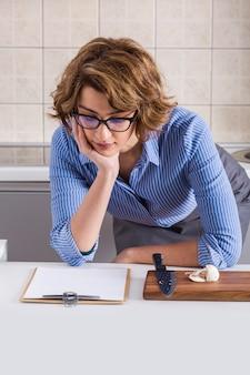 Jovem mulher lendo a receita com enquanto prepara a comida na mesa