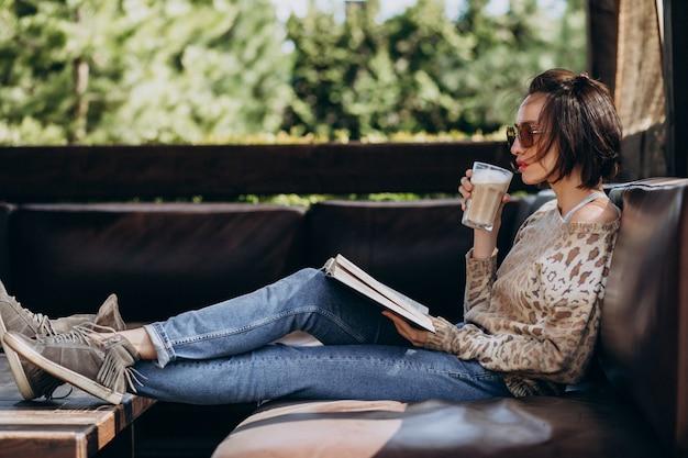 Jovem mulher lendo livro e bebendo café