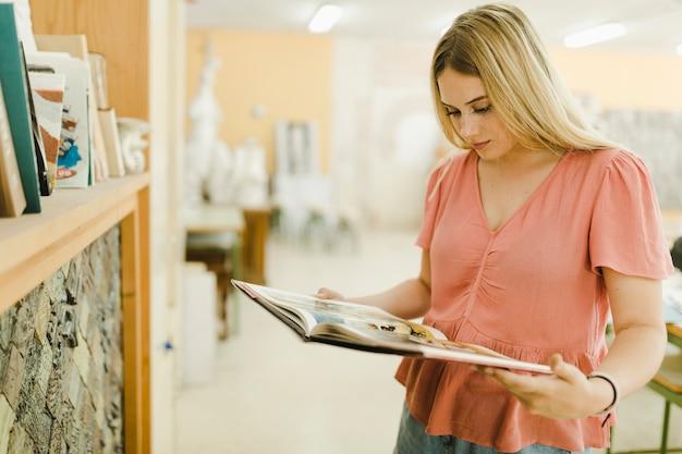 Jovem mulher lendo livros na oficina