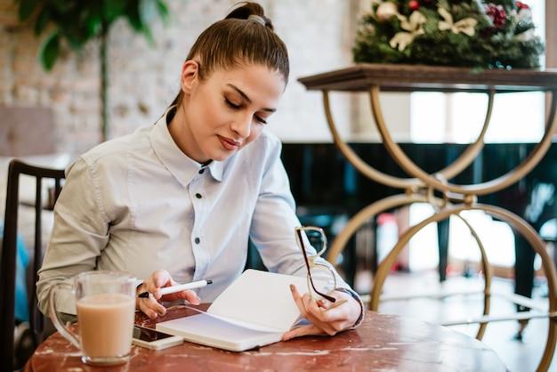 Jovem mulher lendo no café.