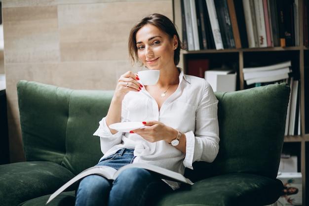 Jovem mulher lendo um livro e bebendo chá em casa