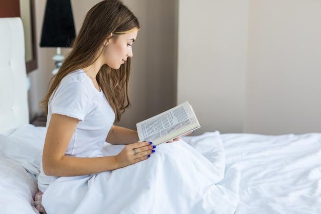 Jovem mulher lendo um livro e sorrindo enquanto se senta na cama.