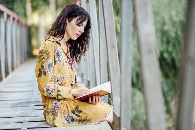 Jovem mulher lendo um livro em uma ponte rural.