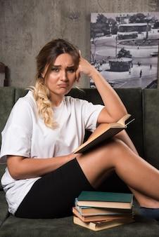 Jovem mulher lendo um livro no sofá com uma expressão entediada.