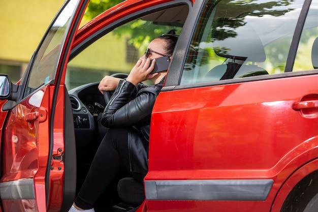 Jovem mulher ligando pelo celular, smartphone na parada da rodovia no carro, conceito de transporte