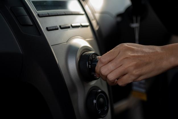 Jovem mulher ligar o sistema de ar condicionado do carro,