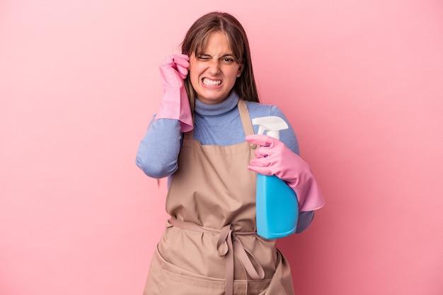 Jovem mulher limpadora caucasiana segurando spray isolado no fundo rosa, cobrindo as orelhas com as mãos.