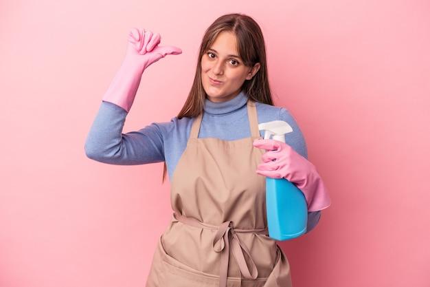 Jovem mulher limpadora caucasiana segurando spray isolado no fundo rosa se sente orgulhosa e autoconfiante, exemplo a seguir.