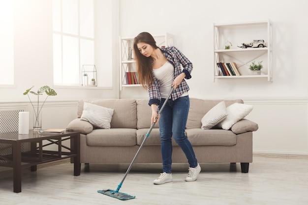 Jovem mulher limpando a casa com esfregão