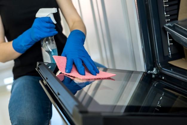 Jovem mulher limpando o forno com luvas de borracha e pano. conceito de limpeza