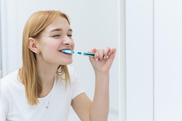 Jovem, mulher, limpando os dentes com escova de dentes no banheiro. higiene oral.