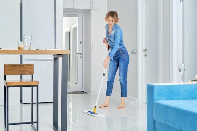 Jovem mulher limpando seu apartamento com esfregão