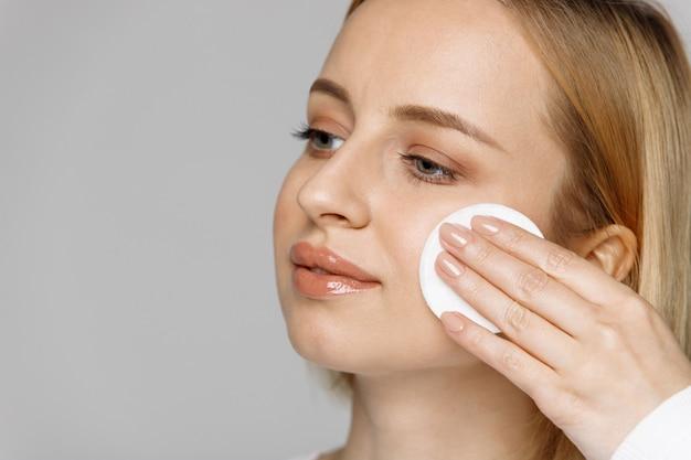 Jovem mulher limpeza (remoção de maquiagem) o rosto com almofada de algodão, fundo cinza.