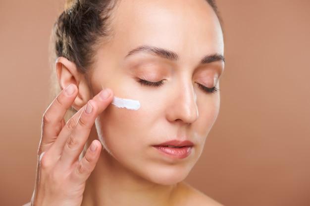 Jovem mulher linda aplicando creme facial rejuvenescedor na área sob os olhos enquanto cuida de sua pele pela manhã ou antes de dormir Foto Premium