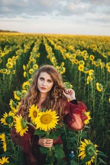 Jovem mulher linda em um vestido entre girassóis florescendo. agro-cultura.