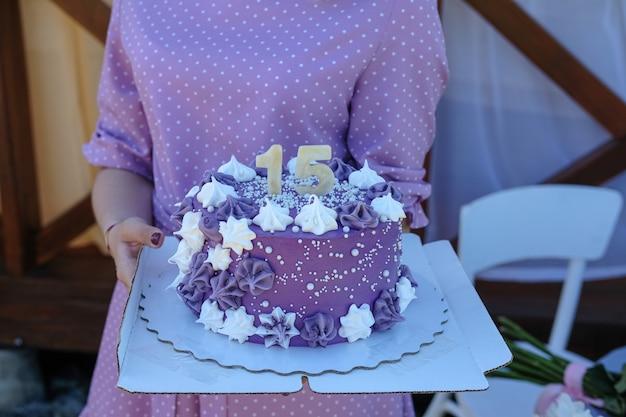 Jovem mulher linda em um vestido roxo segurando um bolo de aniversário com o número quinze, decorado com creme roxo e merengue