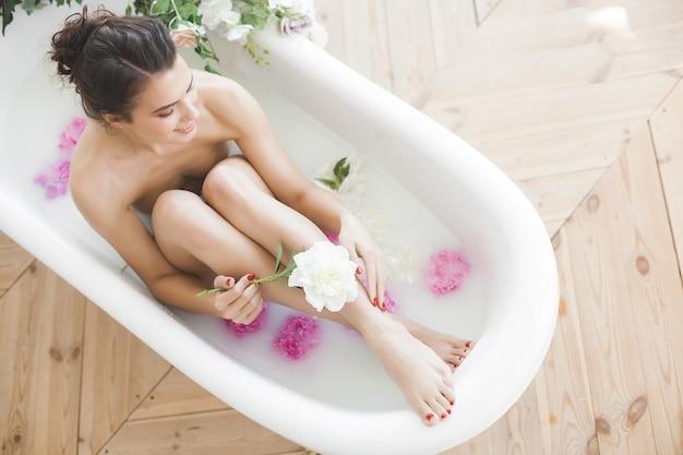 Jovem mulher linda tomando banho com flores e leite