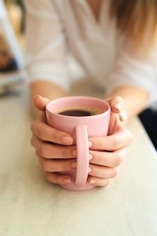 Jovem mulher linda tomando café ou chá