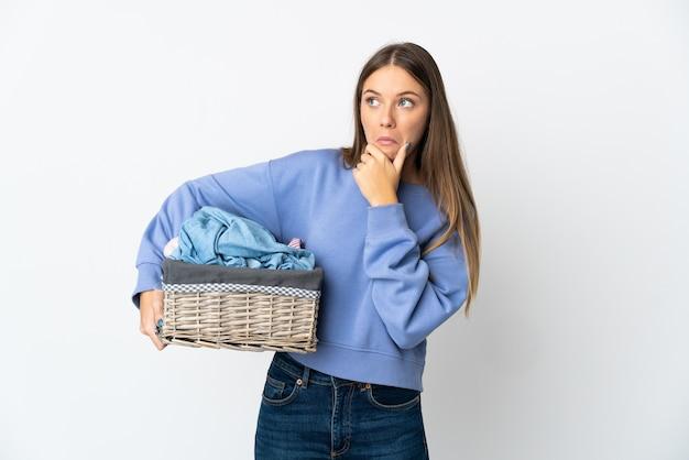 Jovem mulher lituana segurando um cesto de roupas, isolado no fundo branco, tendo dúvidas