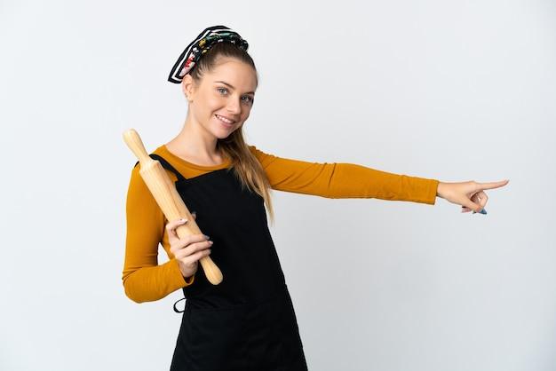 Jovem mulher lituana segurando um rolo de massa isolado no fundo branco, apontando o dedo para o lado e apresentando um produto
