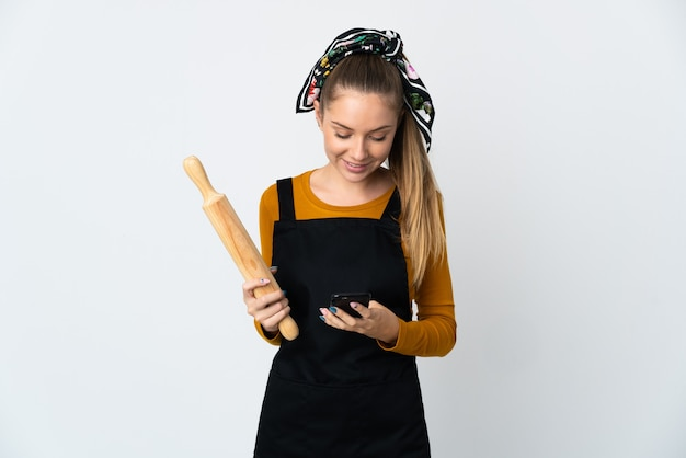 Jovem mulher lituana segurando um rolo de massa isolado no fundo branco enviando uma mensagem com o celular