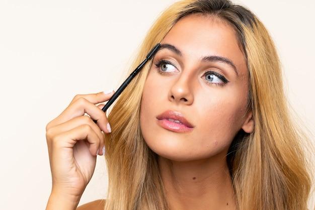 Jovem mulher loira aplicar rímel com pressa cosmética