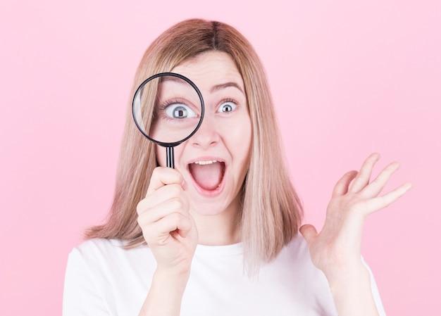Jovem mulher loira atraente chocada ao olhar através de uma lupa sobre a parede rosa.