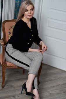 Jovem mulher loira atraente vestindo roupas de negócios, sentado em uma cadeira