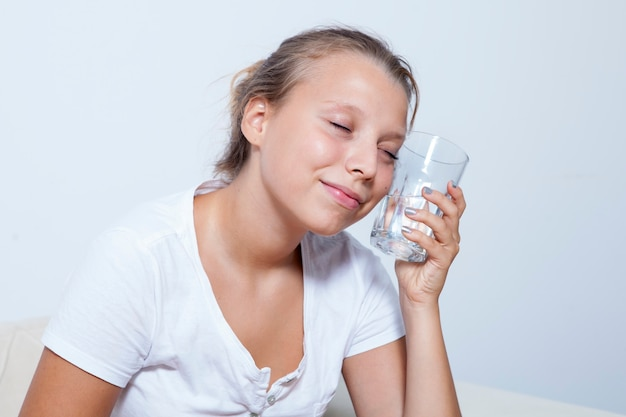 Jovem mulher loira bebendo água limpa segue o regime de beber. conceito de cuidados de saúde.