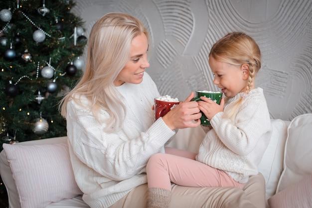 Jovem mulher loira bonita abraça sua filha no sofá com canecas de bebida quente.