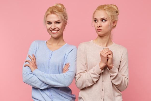 Jovem mulher loira bonita assustada olha para sua irmã alegre isolada sobre fundo rosa.