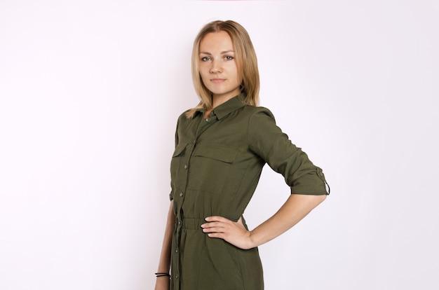 Jovem mulher loira bonita com camisa verde na parede branca. isolado