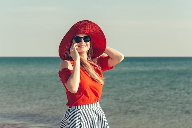 Jovem mulher loira bonita com celular na praia