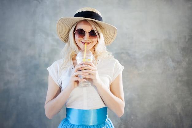 Jovem mulher loira bonita com chapéu de palha. óculos de sol estilo verão.