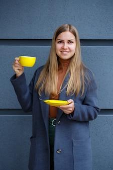 Jovem mulher loira bonita com um casaco cinza bebe chá quente em uma xícara amarela em um dia frio de outono. deliciosa bebida quente na esplanada do café