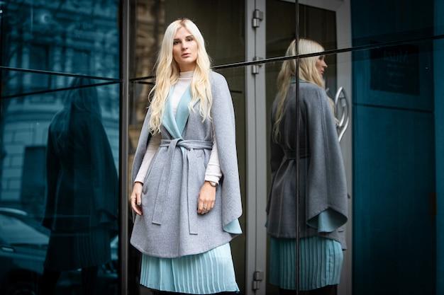Jovem mulher loira bonita com um casaco de outono fica em uma rua da cidade. foco suave. conceito de moda.