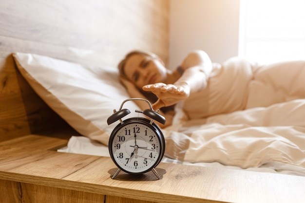 Jovem mulher loira bonita deitada na cama de manhã. ela estende a mão para o despertador. modelo sonolento. irritação. luz do dia de manhã.