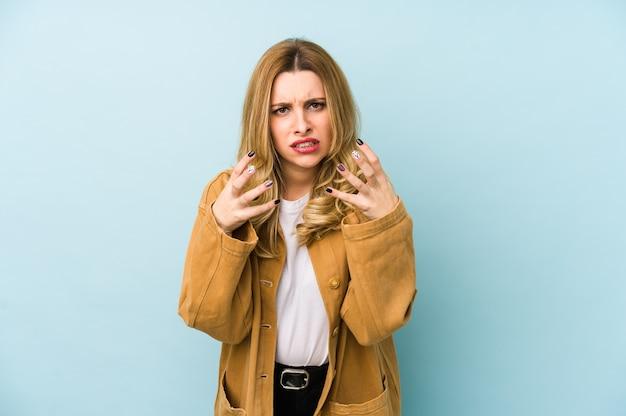 Jovem mulher loira bonita isolada chateada, gritando com as mãos tensas.